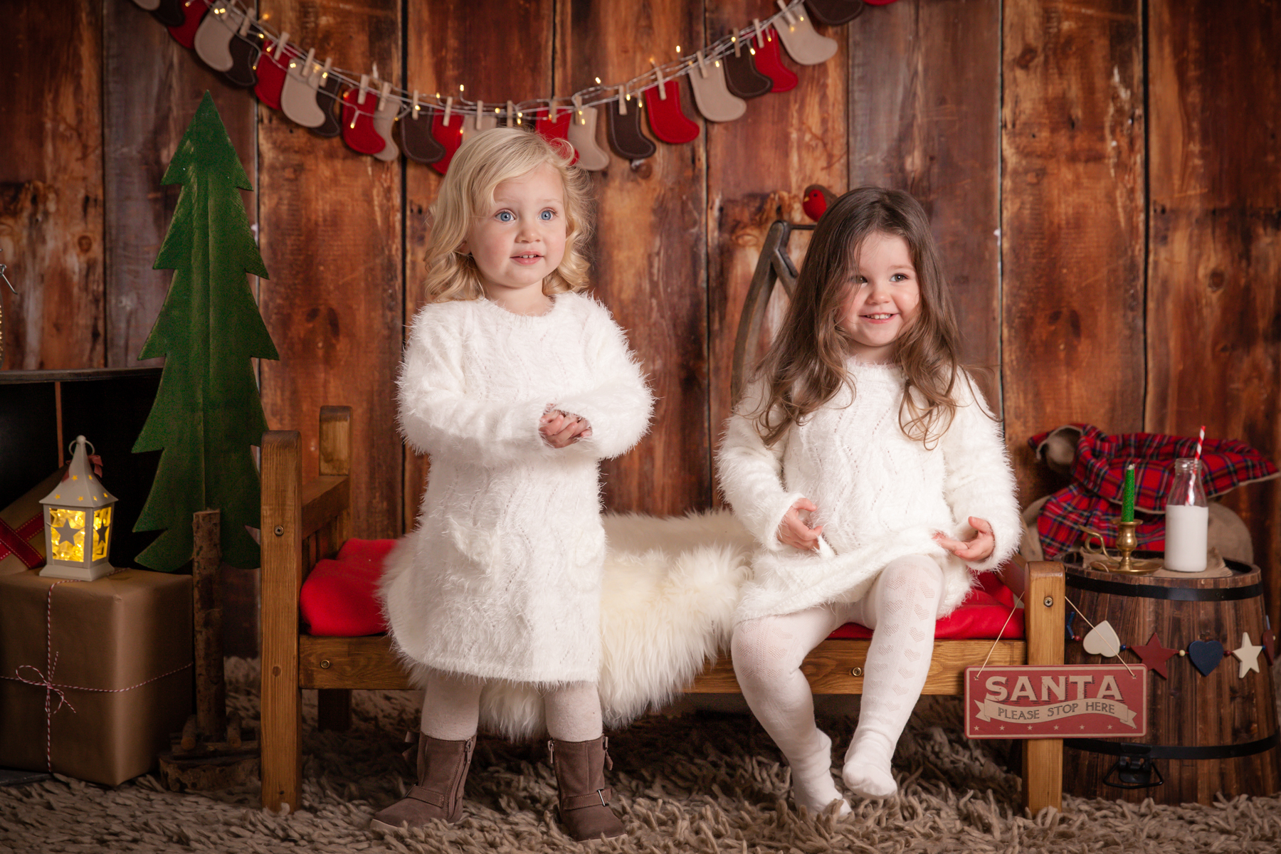 sisters in angelic christmas jumpers waiting for santa