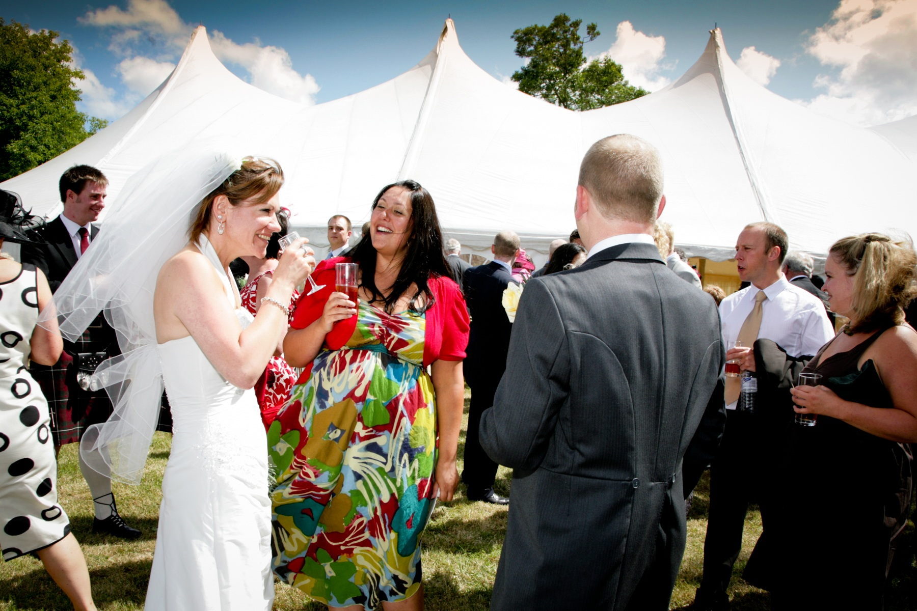 Guests chatting with bride outside marquee in Scottish Borders