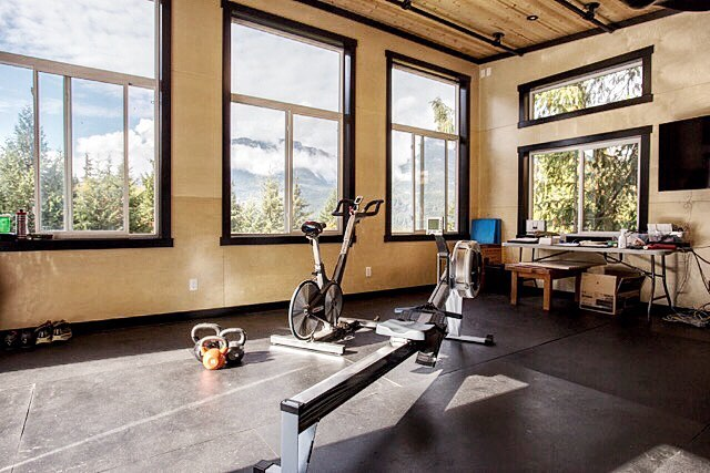 Interior of the gym space. Birch walls contrasted with black trim and black mounting pipes on the ceiling. The rubber floor creates the perfect durable and comfortable finish for all types of activities. Photo credit to #jannickekitchenphotography. #timberwolfhomes #squamish #gym #mountainlife #squamish #tinyhouse #instagood