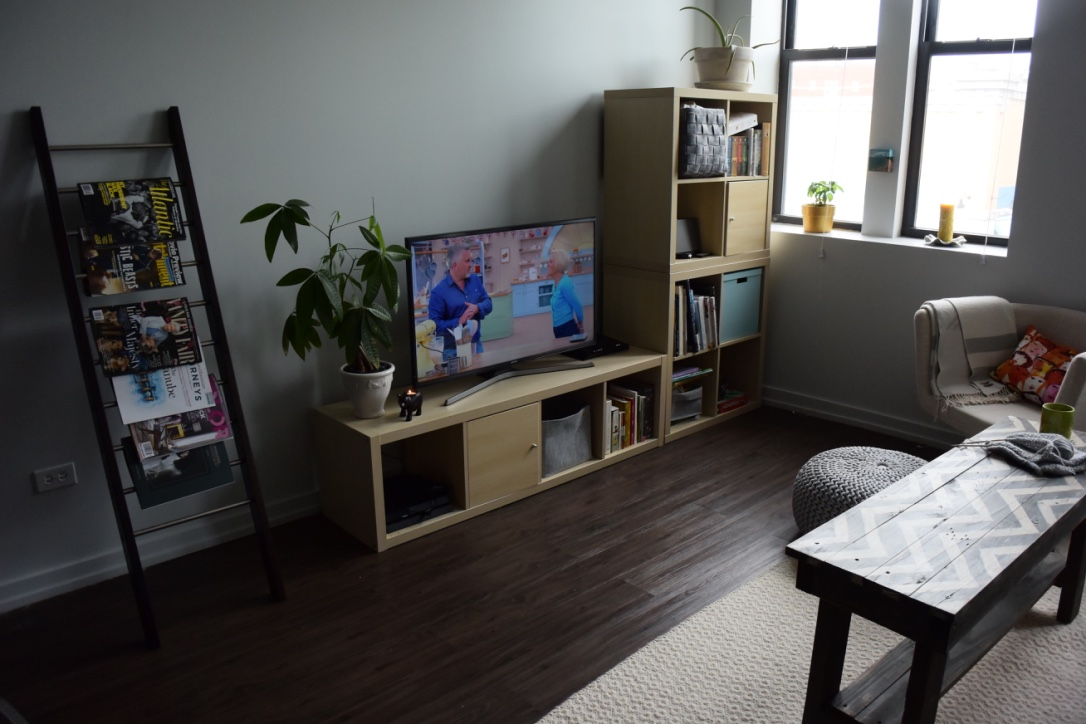 A view of our TV stand/media console composed of various parts of the  KALLAX  series from IKEA. We placed together a few different storage units to make an L, and the cubes are filled with various books, knitting projects, electronics, & more. My favorite part is the aqua box - I think it livens everything up!