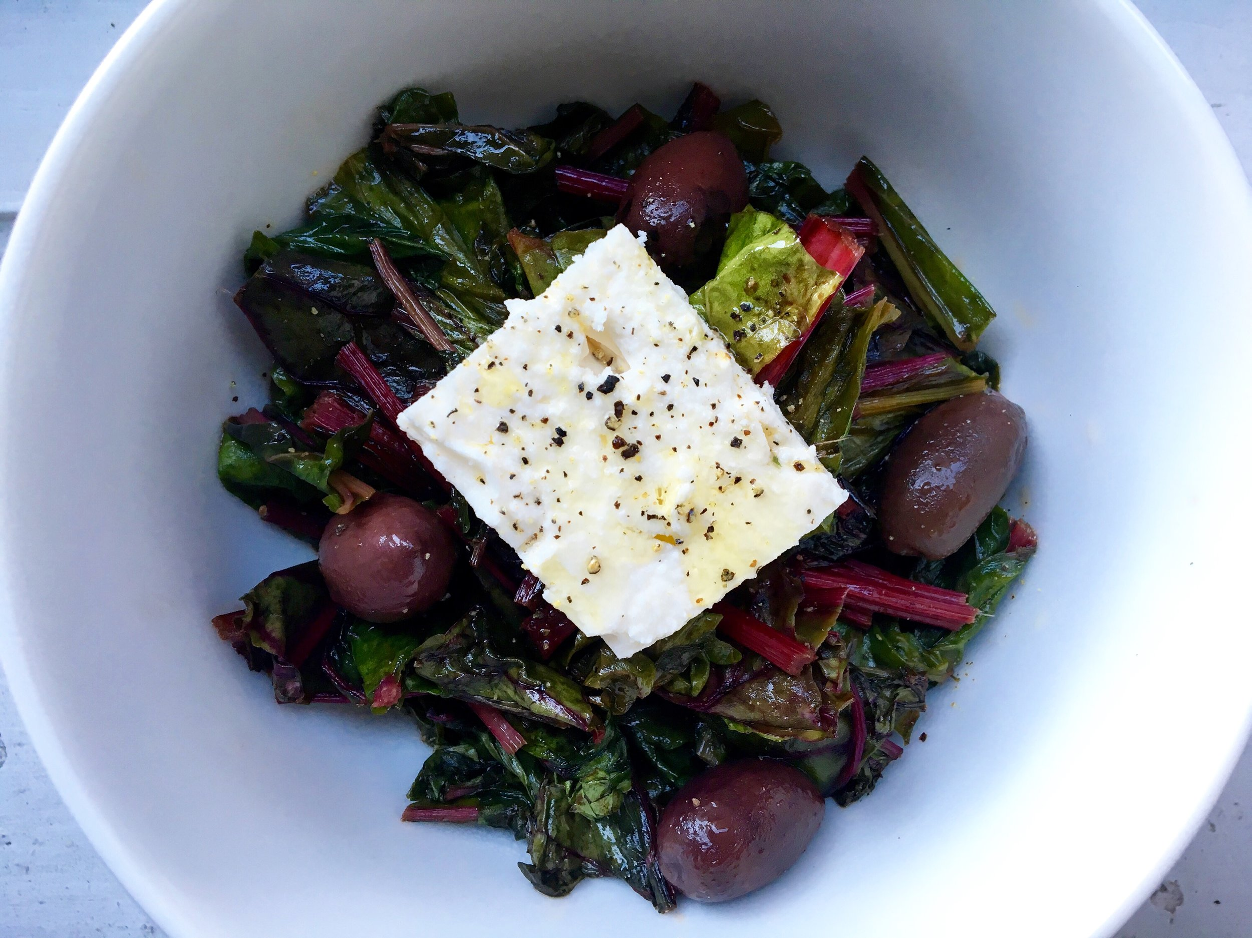 spicy swiss chard saute with red pepper flakes, garlic + olives (topped with a block of feta)
