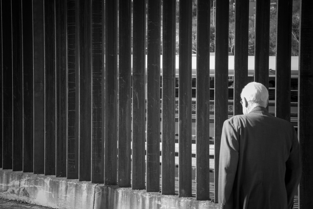 Rev. Dr. Ken Bensen ponders the immigration issue from the Mexico side of the U.S. Border wall.