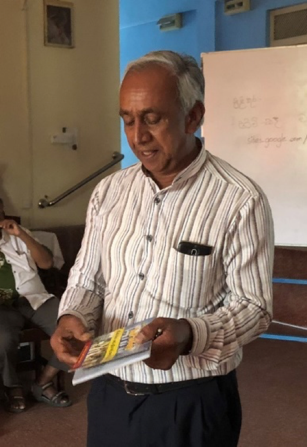 Mr. Dharmasena shows off the program book from a concert that netted Rs. 30 million.