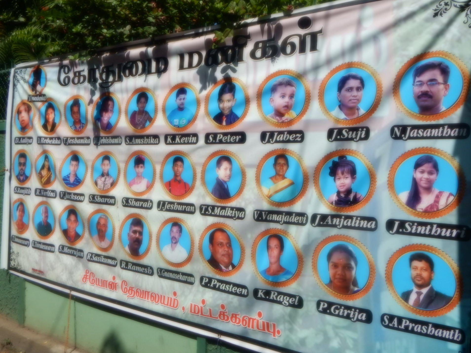 A banner with names and faces of the victims of Easter Morning bomb blast hangs in the church yard.