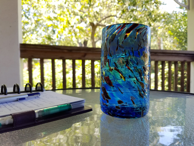 Glass for refreshing beverage next to my ever-present notebook. And pen. On the Front Porch.