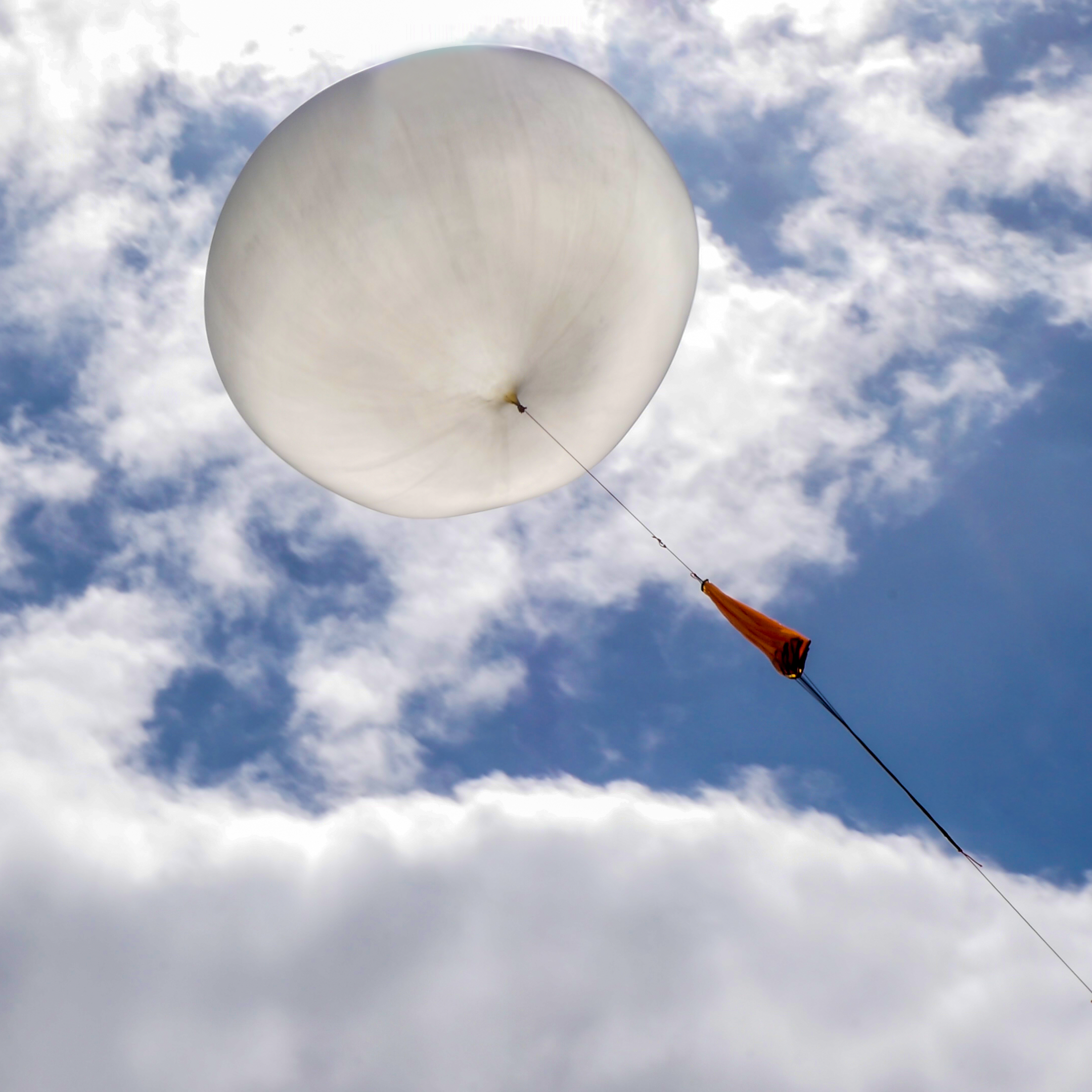A latex meteorological balloon against a blue sky with clouds