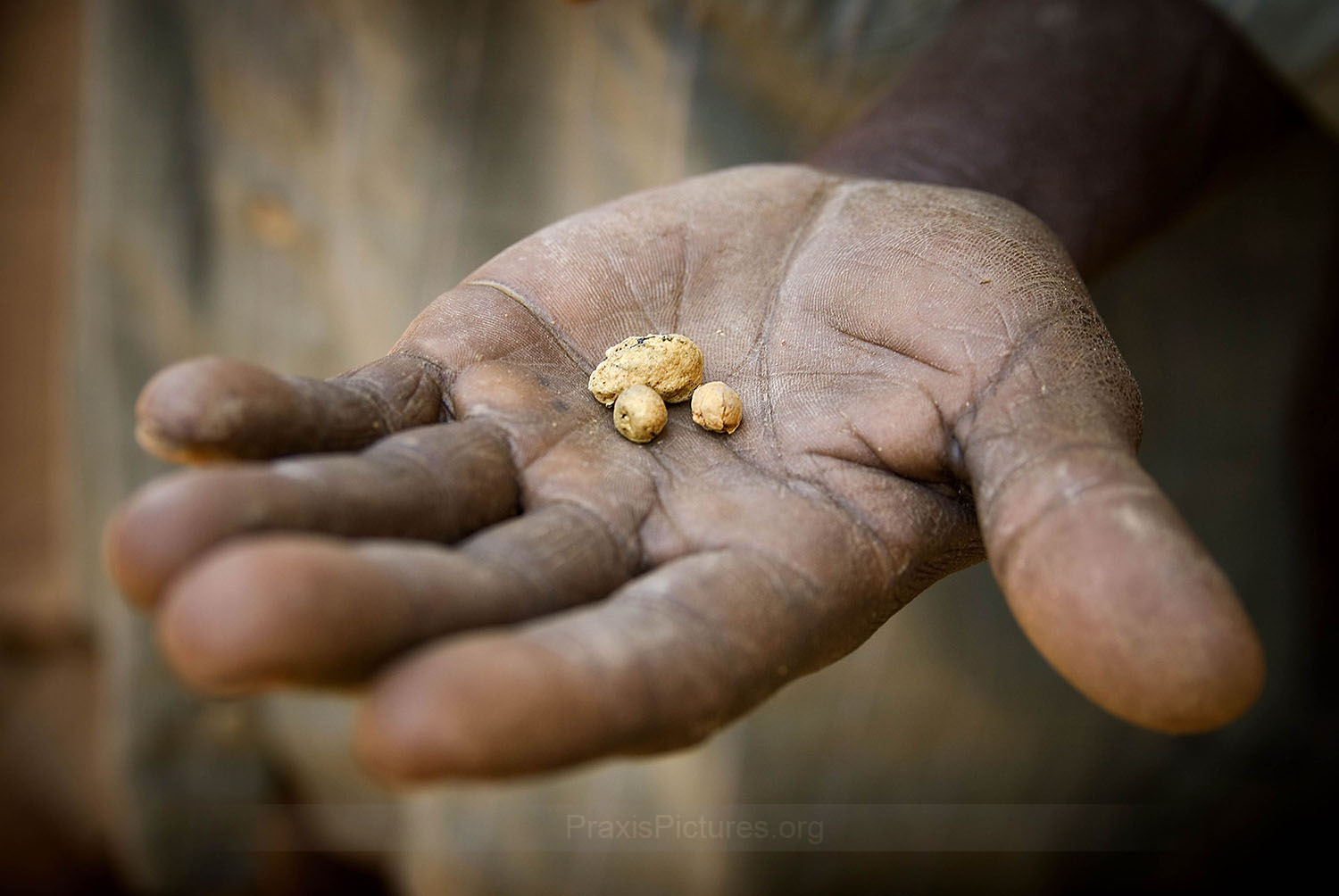 THE PRICE OF GOLD - An artisanal miner in Tanzania holds out some gold nuggets. The price of gold has been skyrocketing, reaching record high prices in recent years. Multinational mining companies search the ends of the earth for these, and other, valued natural resources. Meanwhile, the people who just happen to live there are the ones who usually end up paying the price. For minerals that mean little to them, for profits they never see, the price they pay includes the very things that they treasure most – including the loss of traditional lands, livelihoods, health, culture, and loved ones.