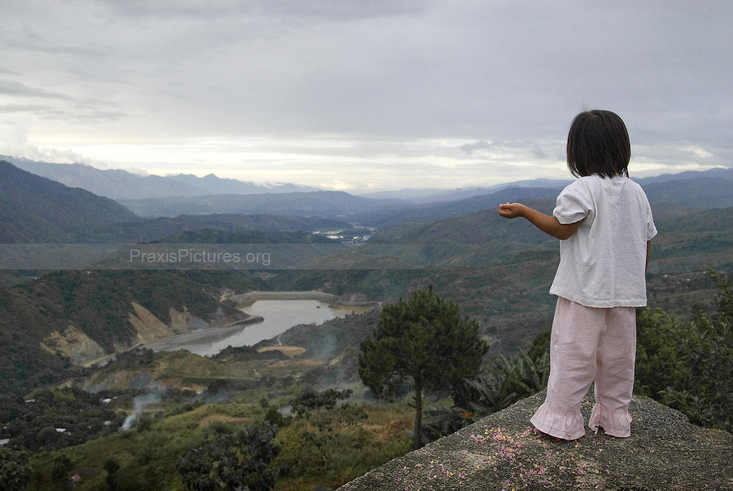 TRIXIE - Standing a few meters away from her home in Benguet province, Philippines, Trixie looks down at the tailings dam of the Victoria Gold Mine where the toxic waste from the mining process is dumped at a rate ranging between 1,500 and 2,500 metric tons per day. This is the third dam built here after the previous two collapsed. This particular dam has been completely inadequate against the torrential downpour during the yearly rainy season and is especially vulnerable to earthquakes as Benguet is directly above a fault line. For years the chemicals have been leaking out into the nearby river systems.