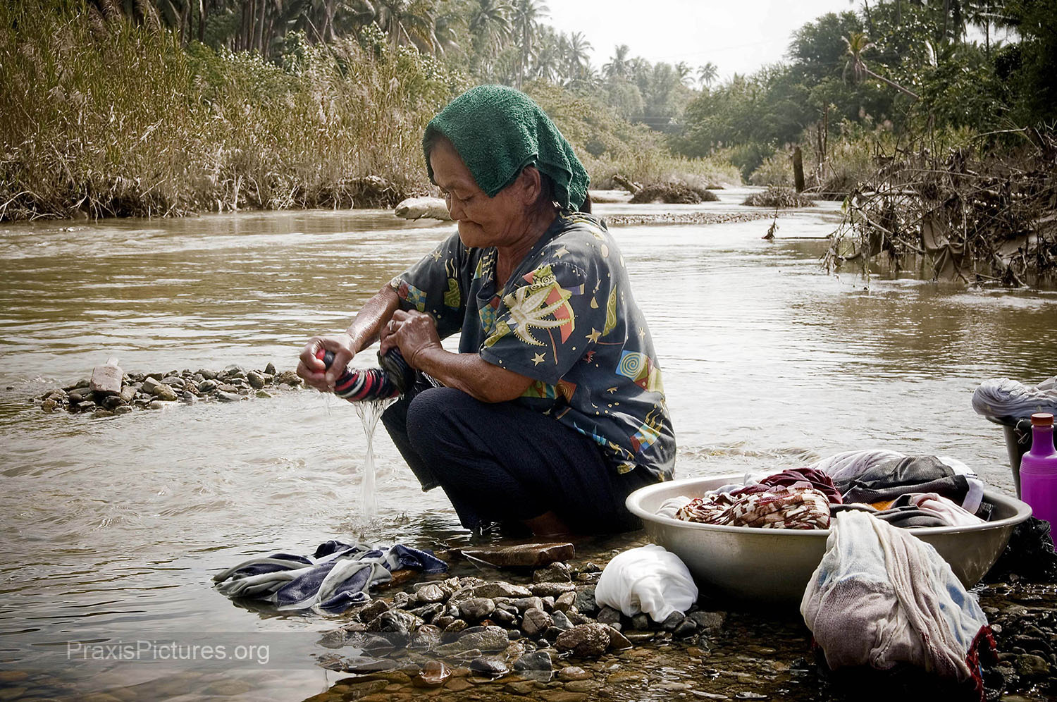 REMY - Remy washes her laundry in the poisoned Mogpog River in the Phillippine island of Marinduque. In 1993 one of the tailings dams of the Marcopper Mine burst sending tons of mine waste raging down the river in a flash flood sweeping away homes, people and livestock. Three years later a second collapse sent waste in the opposite direction destroying the Boac river. To this day both of the islands main rivers remain biologically dead and contain dangerous levels of toxic chemicals. Dead trees and other debris can still be seen all along the rivers. But people here have no other water sources to rely on.