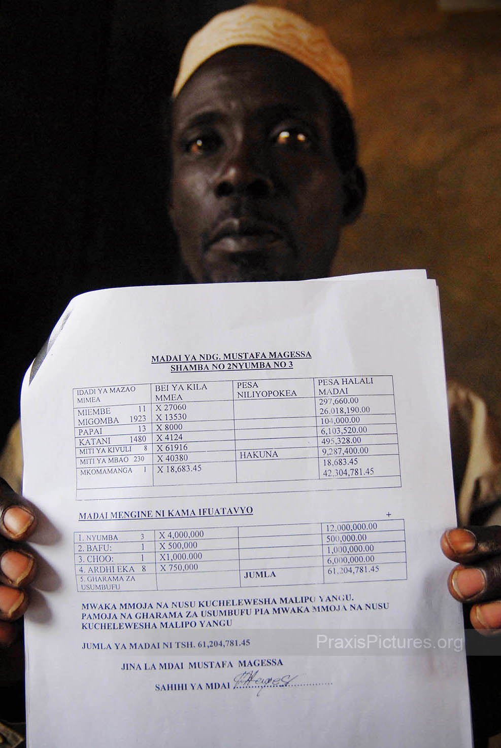 "MUSTAFA - The government's Prevention of Corruption Bureau is investigating a corruption scandal involving the compensation for some 900 people who were displaced to make way for AngloGold Ashanti's Geita Gold Mine in Geita.  Mustafa is one of the complainants; here he is showing documents that state that he was promised over 60million shillings (55,000CAD) in compensation which he has never received.  AngloGold admits that 875 people have not received the compensation promised to them, but they claim to have given government officials the money needed to make the payments in 1999 and blame these officials  ""in their lust for money""  for the disappearance of the funds."