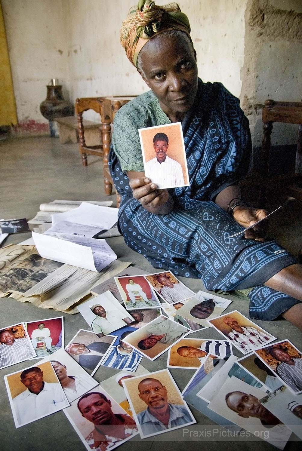 "MELANIA - In response to the companies' and the government's denials Melania, a Kahama resident, has been collecting these photos of people who claim to have witnessed the killings or lost loved ones during the evictions.  ""…This one was there when it happened … this one lost her son … this one went back afterwards to try and dig out his friends … this one lost her home and her grandchildren …""   A number of organizations have been calling for an independent inquiry to resolve the controversial issue including Amnesty International, the Council of Canadians, Mining Watch Canada, the New Democratic Party, Friends of the Earth, and Rights and Democracy. But when an international NGO fact-finding mission attempted to visit Bulyanhulu to investigate the allegations they were barred from entering the area by an armed roadblock, they reported that they were intimidated by the police and were given the impression that they were  ""under surveillance and could possibly be apprehended.""   Melania's two eldest sons, Jonathan and Ernest were among the fifty-two miners who were allegedly buried alive during the evictions. The family owned the pit that they were working in at the time, so Melania lost her livelihood as well as her two children in August 1996.  In a recent report published by religious groups in Tanzania it estimated that  ""that the concentration of gold mining in the hands of large multinational companies at the expense of small-scale artisan miners has put 400,000 people out of work."""
