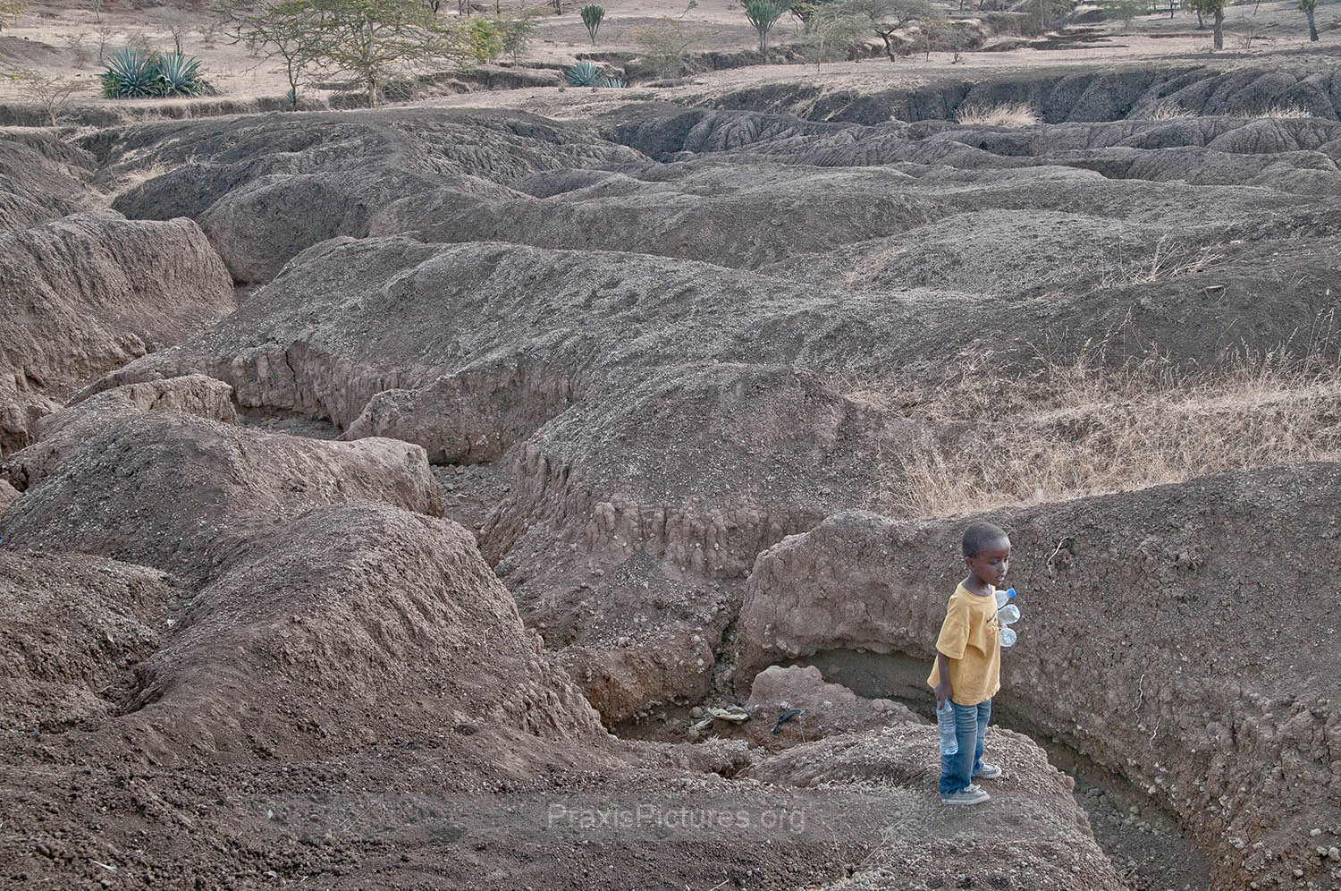 SOIL EROSION - The parched earth has altered the landscape surrounding Ngorbob. Once green fields have eroded leaving the area dangerous for the local children like Baraka.