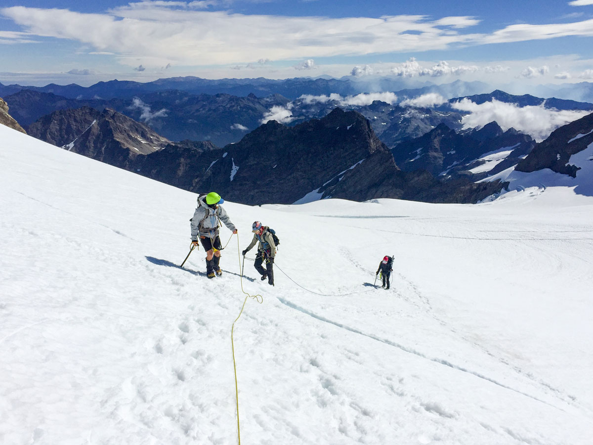 Adding snow to your adventure requires the proper gear and the knowledge of how to use it. Here, Meghan and her friends safely travel glaciated terrain with crampons, rope, and ice axes. Picture: Meghan Young