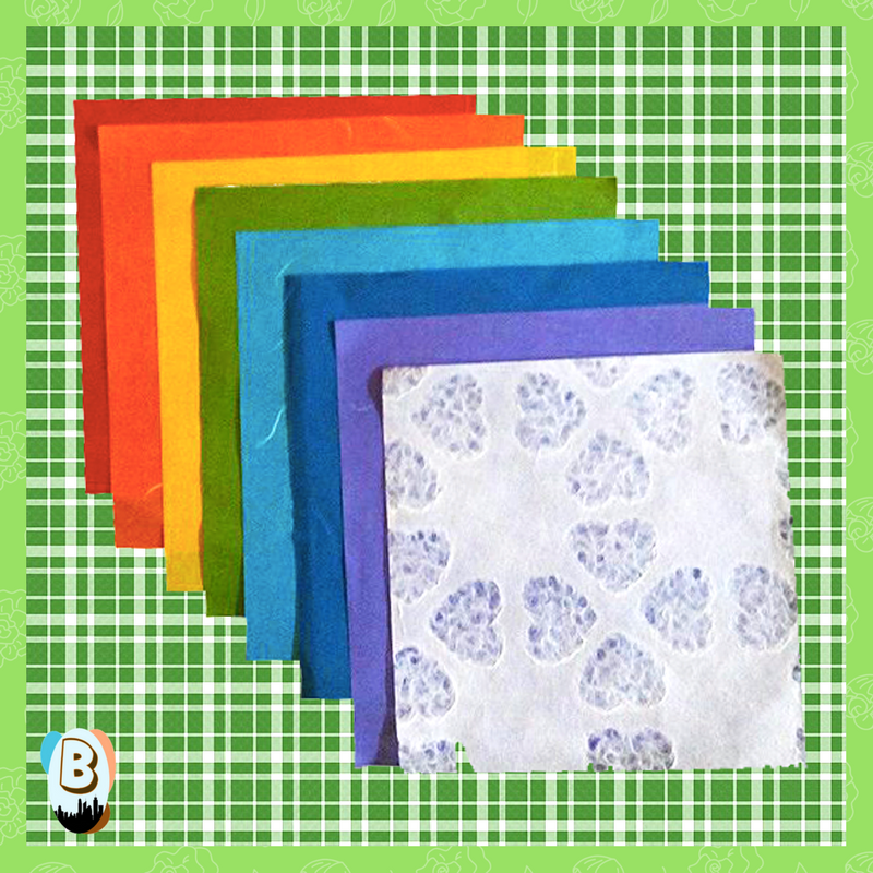 STep 1:  Start out with a rainbow of colored paper. I used oragami paper for the size and texture. Feel free to use white decoration paper or cotton balls since we will be using them for the clouds.