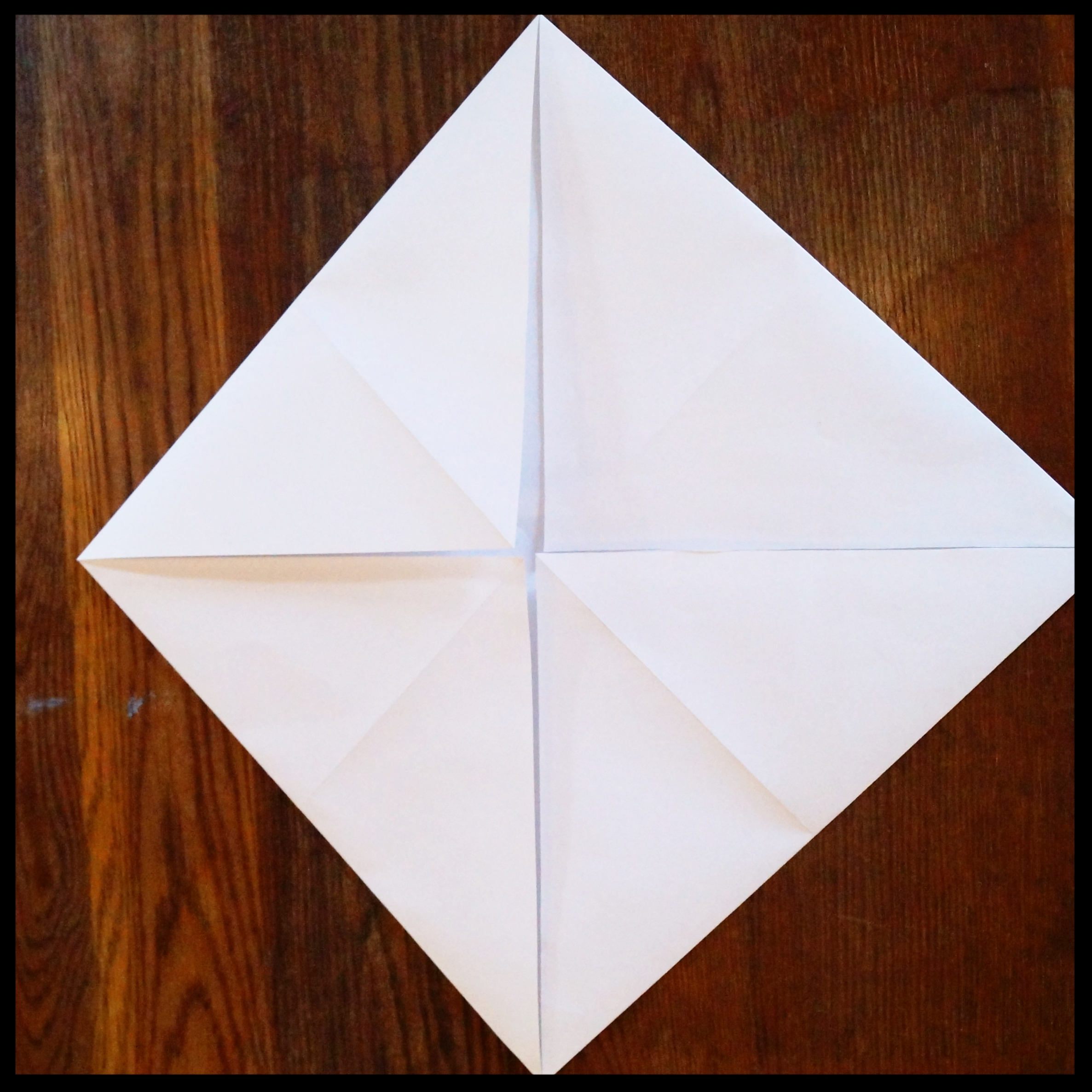 1b. With the paper unfolded back into a square, fold each corner into the center. Do not unfold these.