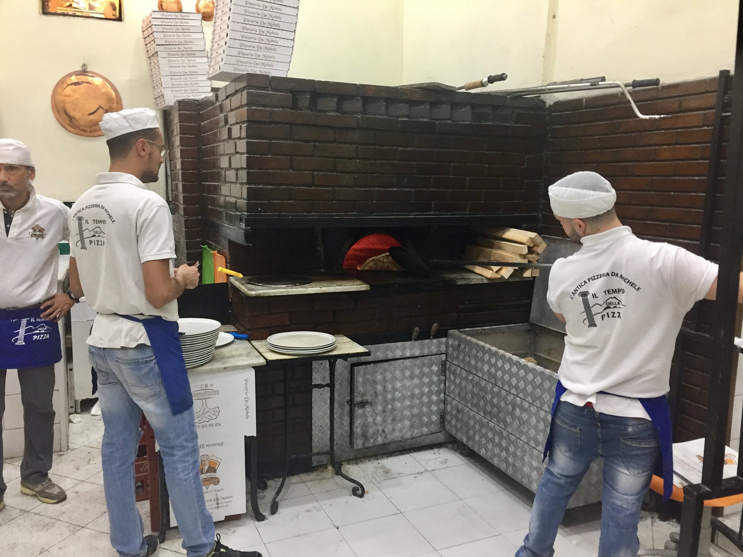 The wood burning oven and hardworking pizzaioli at the legendary L'Antica Pizzeria Da Michele