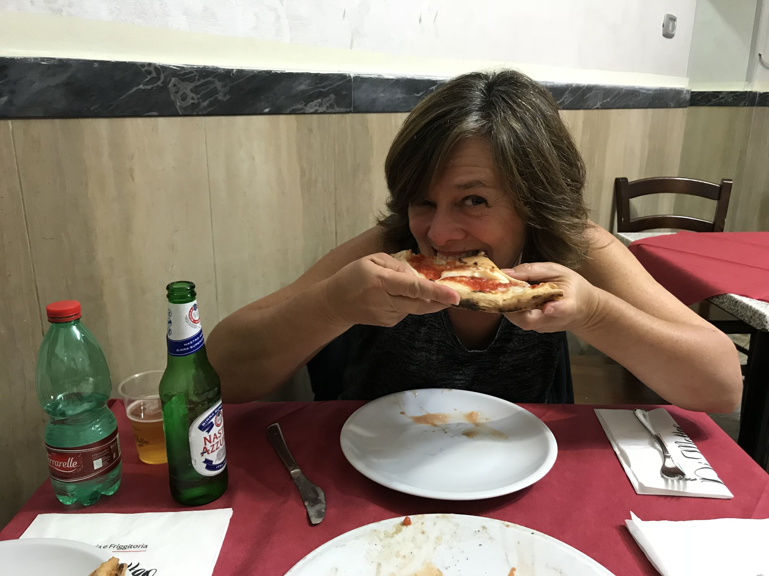 Betsy eating a slice of Margherita pizza at Di Matteo