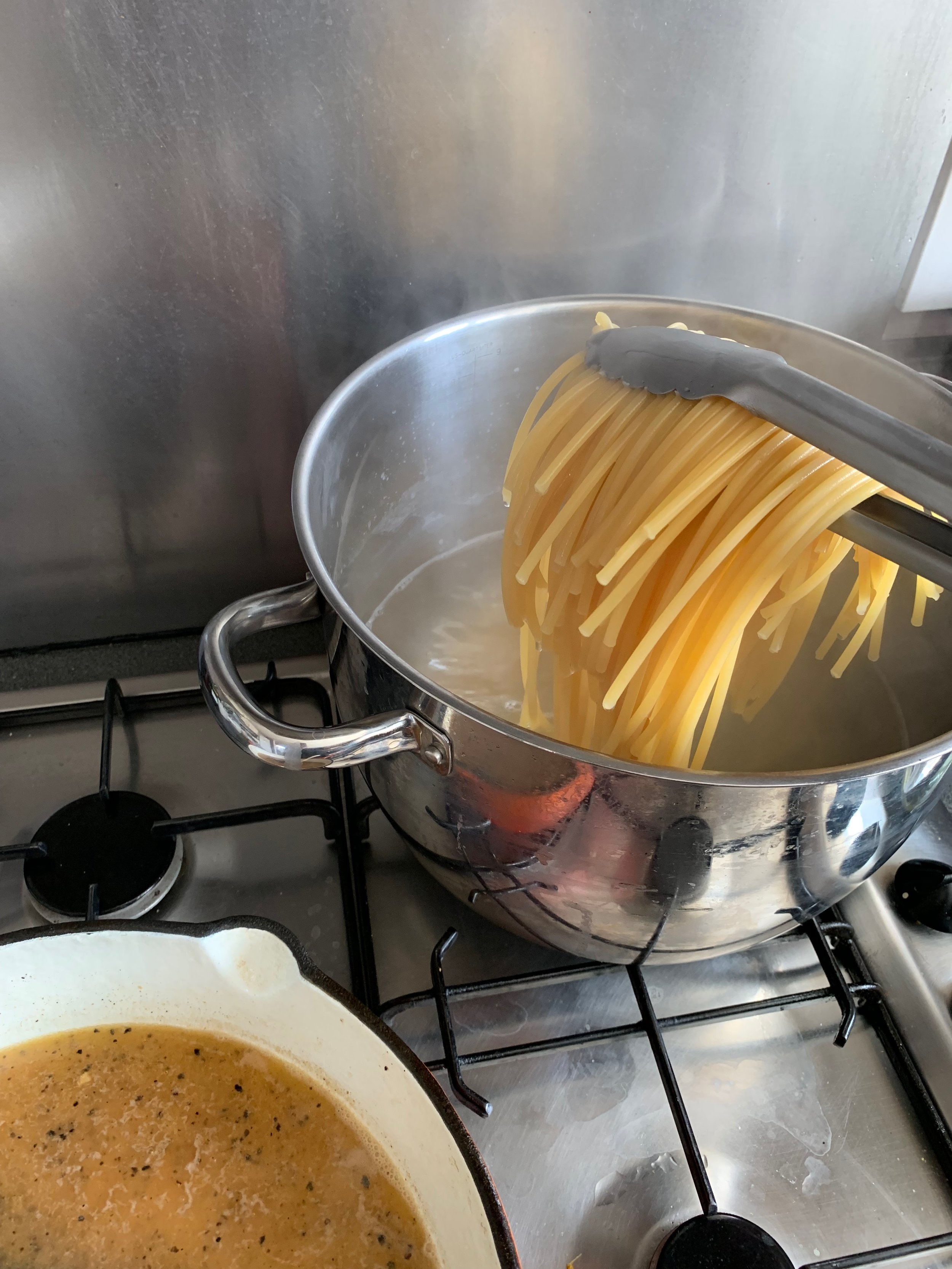 Pasta getting transferred to the skillet