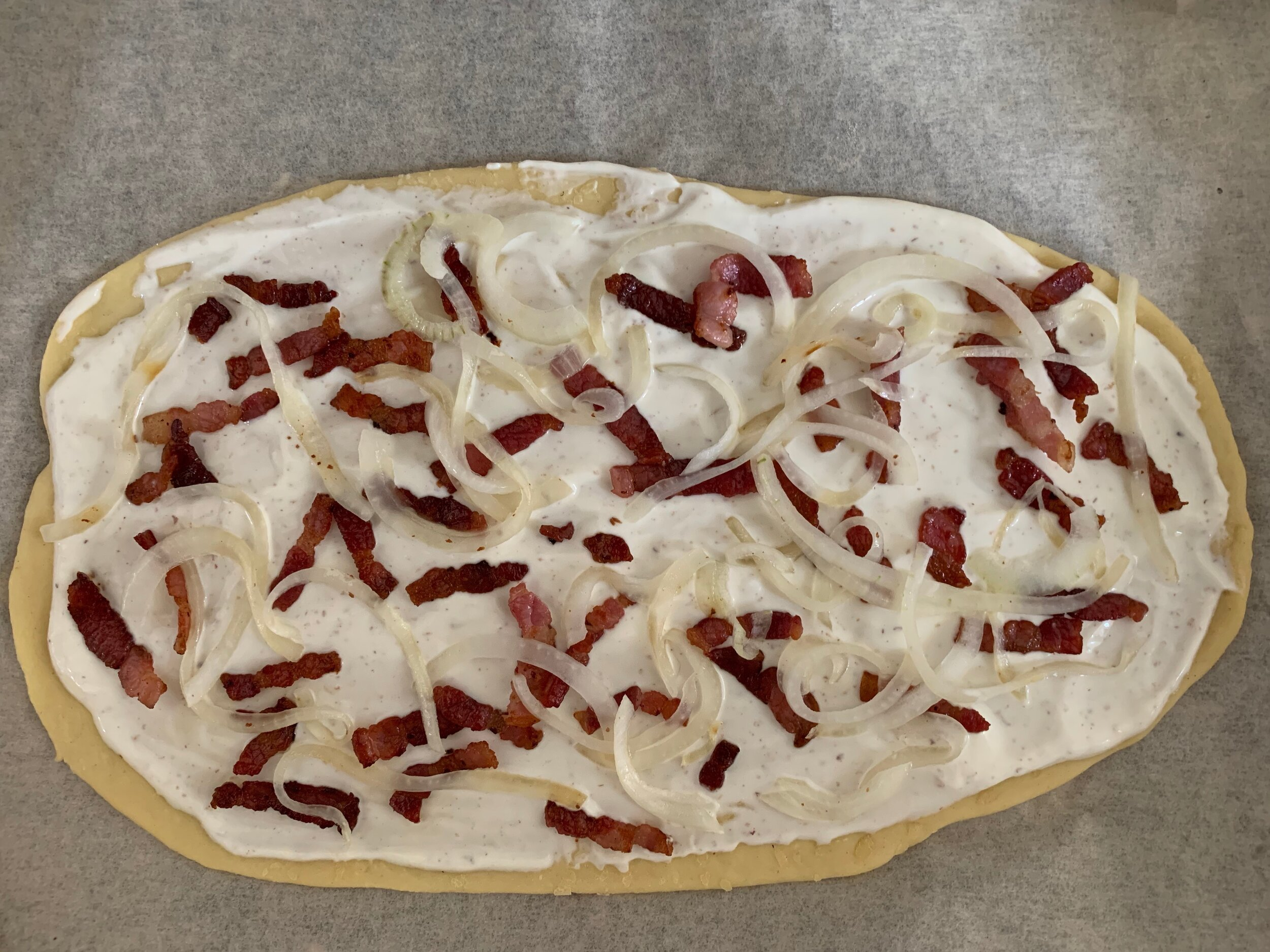 Assembled tarte flambée ready to go in the oven