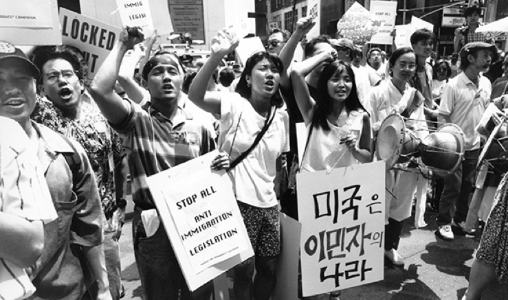 """Asian/Asian American activists rallying for immigration rights. One of the signs reads """"America is the land of immigrants"""""""
