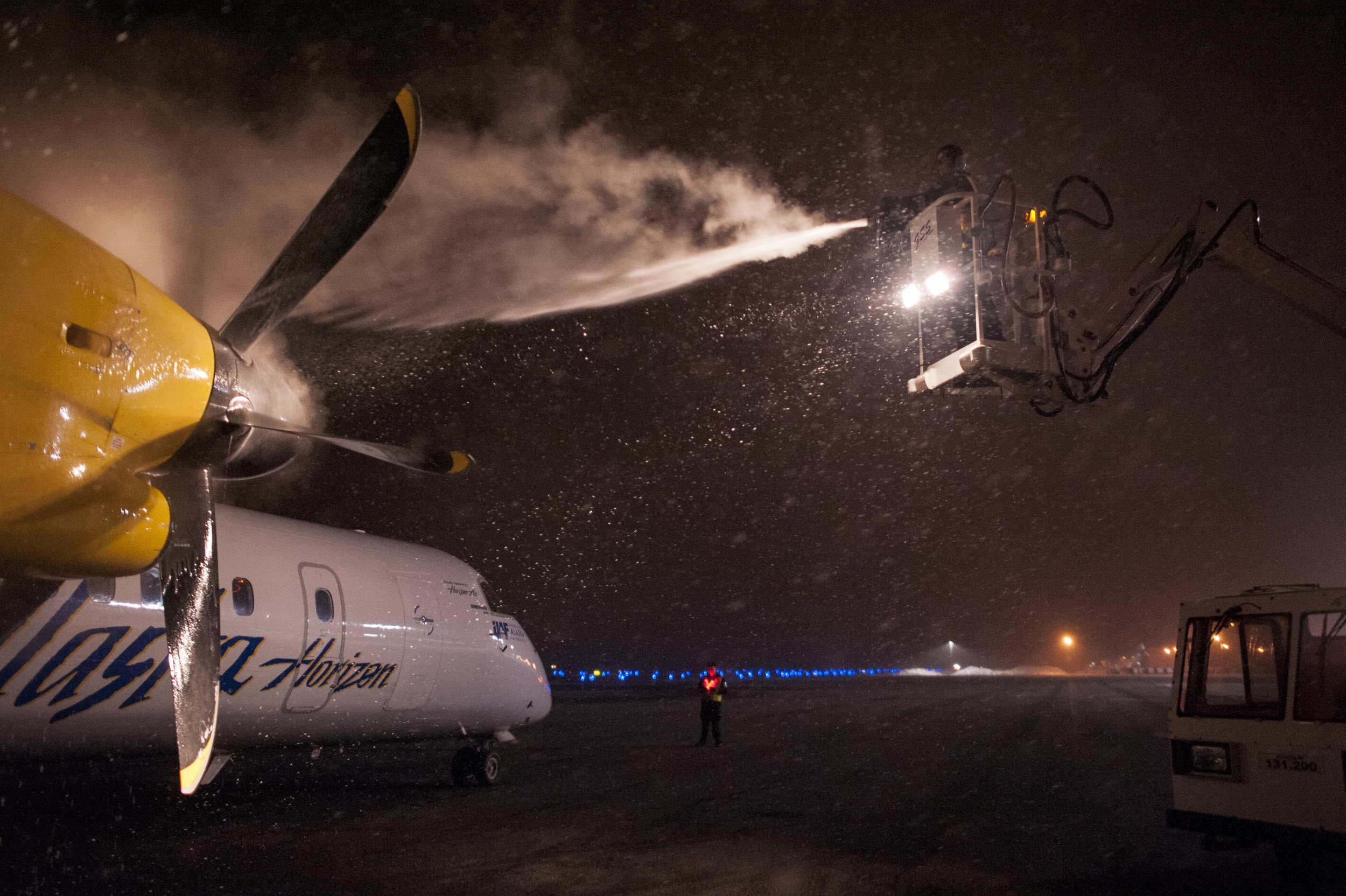 A ramp agent at Bozeman Yellowstone International Airport deices a Q400 destined for Seattle, Wash. Sunday, Feb. 26, 2017.