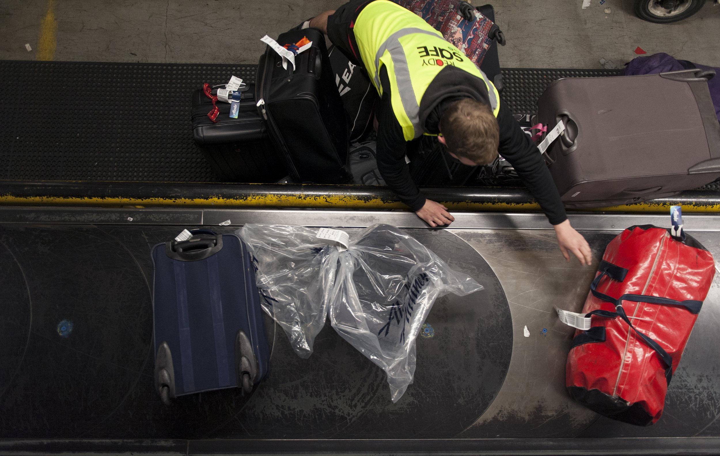 A baggage handler at Seattle - Tacoma International Airport sorts TSA screened baggage Monday, Mar. 20, 2017.