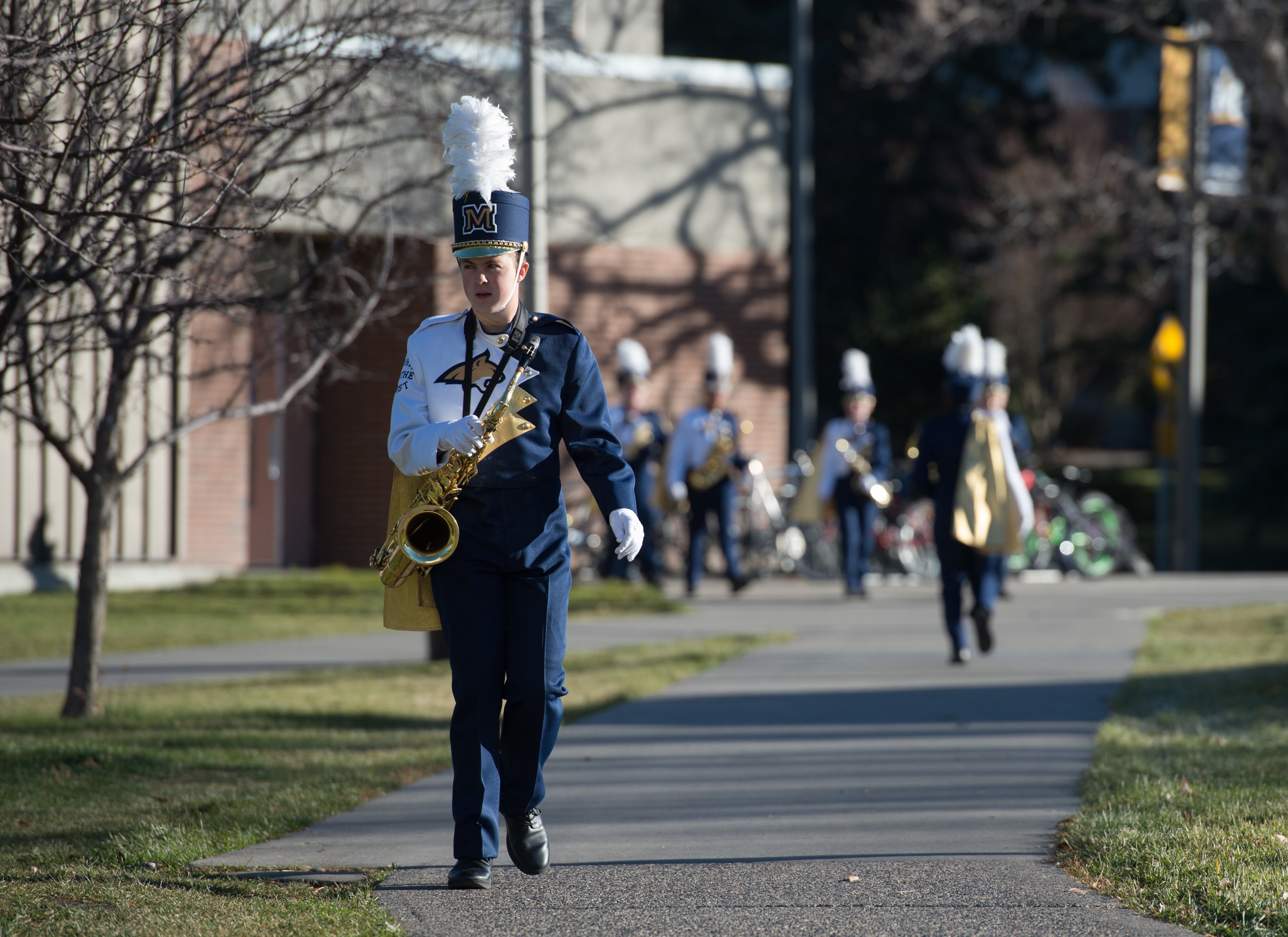 Spirit of the West tenor saxophonist Brandon Stinson heads for the practice field for warmups prior to a game day performance Saturday, Oct. 28, 2017.