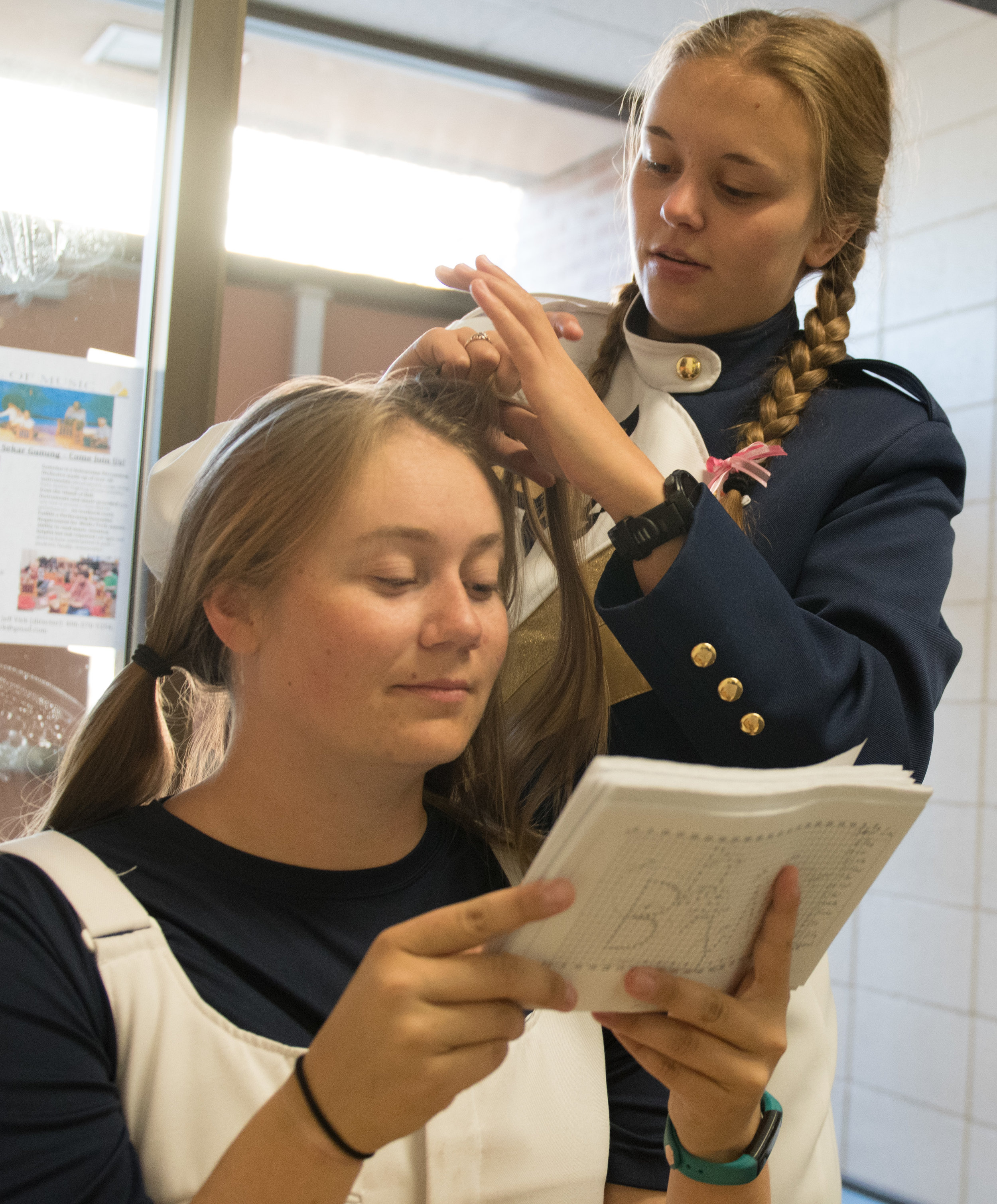 Spirit of the West drum major Jessica Johnson, front, looks over position diagrams while fellow drum major Kendra Hergert, back, braids her hair in preparation for a game day performance Saturday, Oct. 28, 2017.