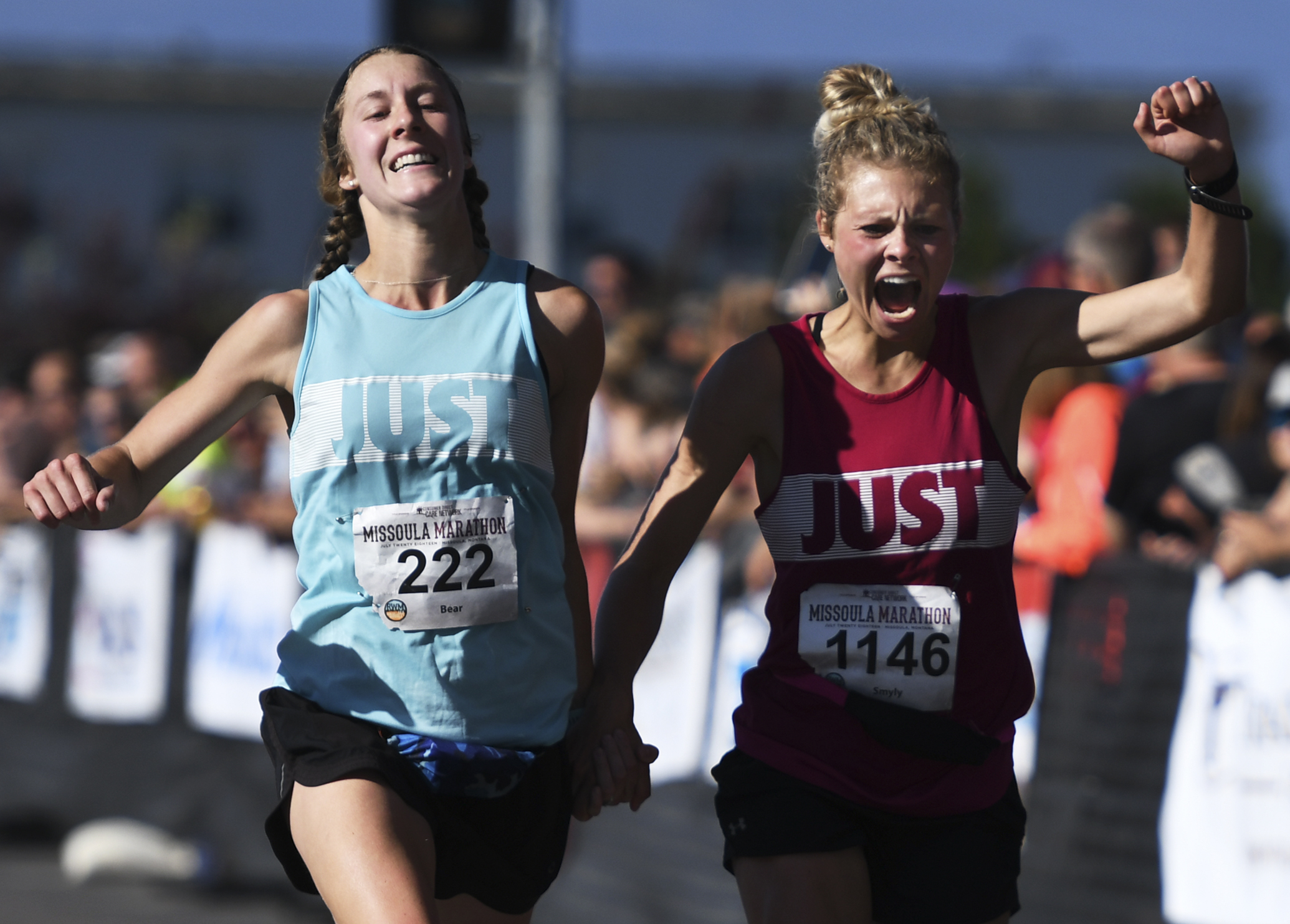 Blair Brady (222) and Sydney Smyly (1146) react as they cross the finish line for the full marathon on the Higgins Street bridge Sunday morning. Smyly and Brady finished with a chip time of 3:17:53.42.