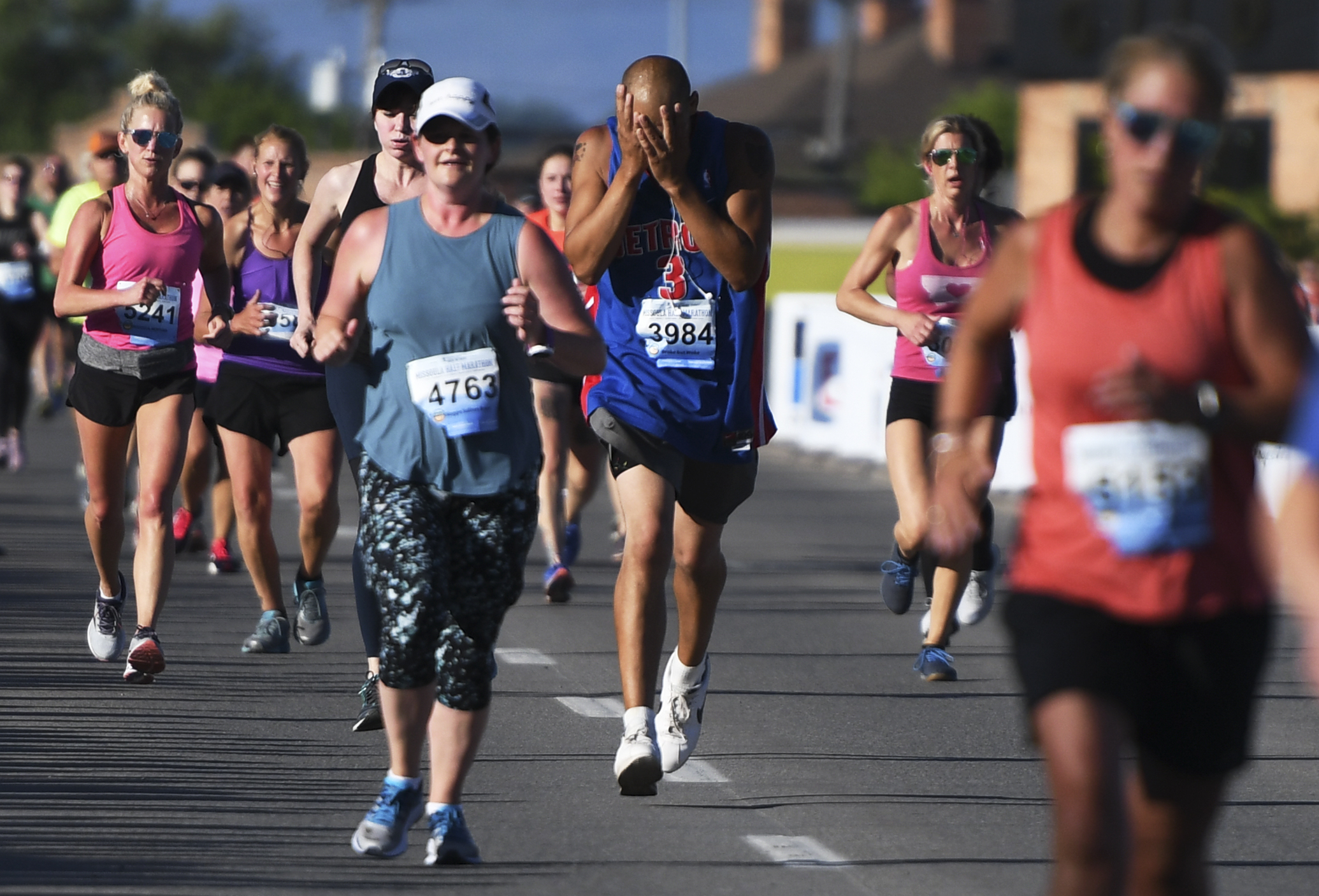 Davie Mizerek (3984), from Odesa, Wash., wipes the sweat from his face as he approaches the finish line for the half marathon on the Higgins Street bridge.