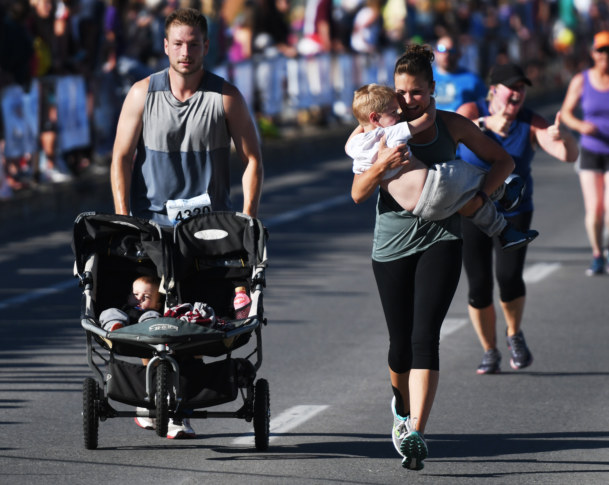 Brittany Rainey carries her son across the finish line for the half marathon while her husband Shaun Rainey (4320) pushes the stroller with their other son.