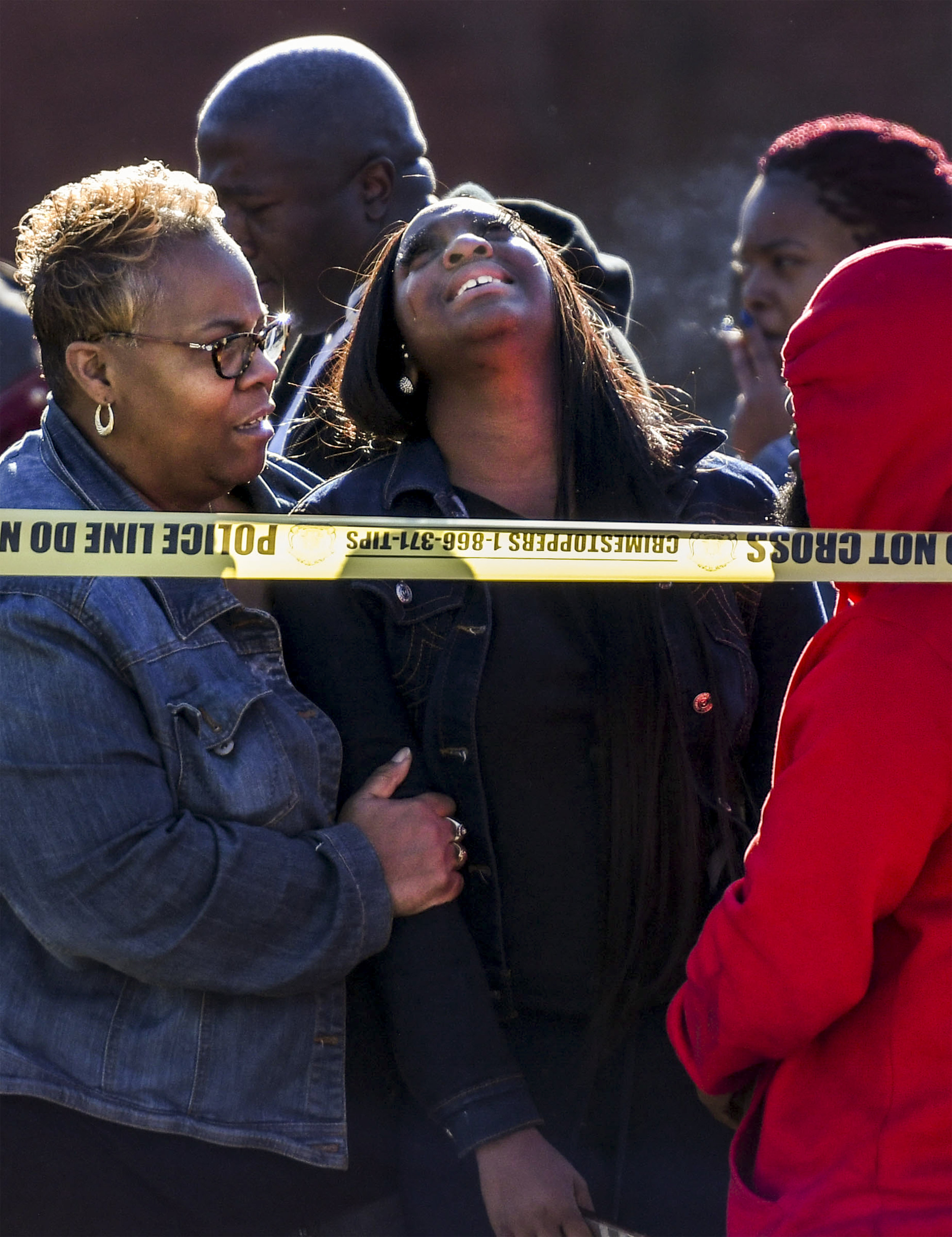 Women console one another near the scene of a triple shooting at the 5600 block of Minerva Avenue on Thursday, Jan. 3, 2019.