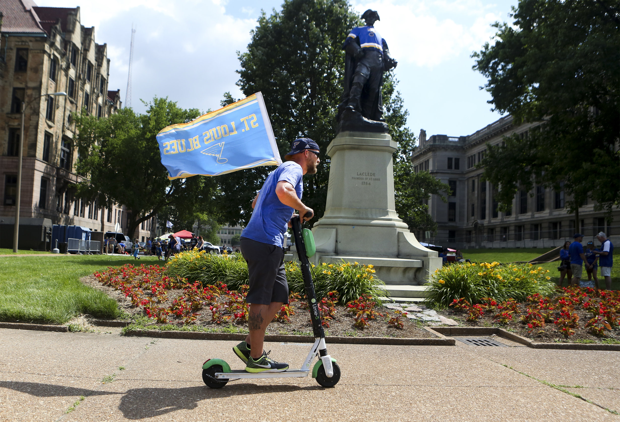 A Blues fan rides a Lime scooter down the sidewalk along Market street before the Stanley Cup Finals game 6 on Sunday, June 9, 2019.