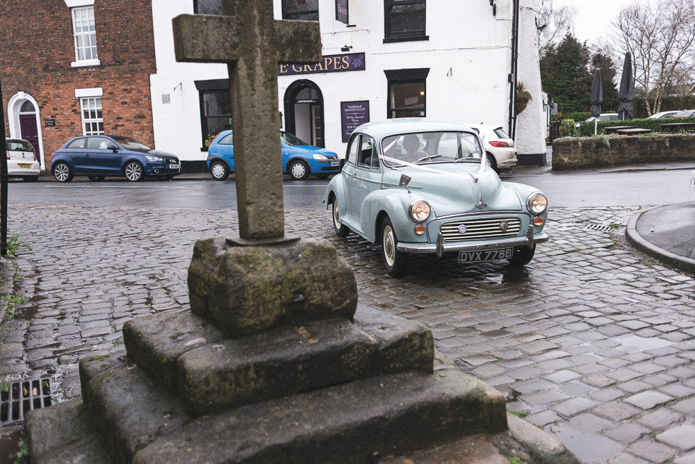 Bride arrives for the wedding service in vintage car, at St Michael's Church Croston