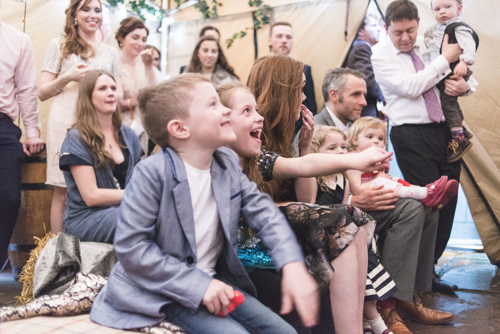 Children laugh during wedding punch and judy show in Croston Old School