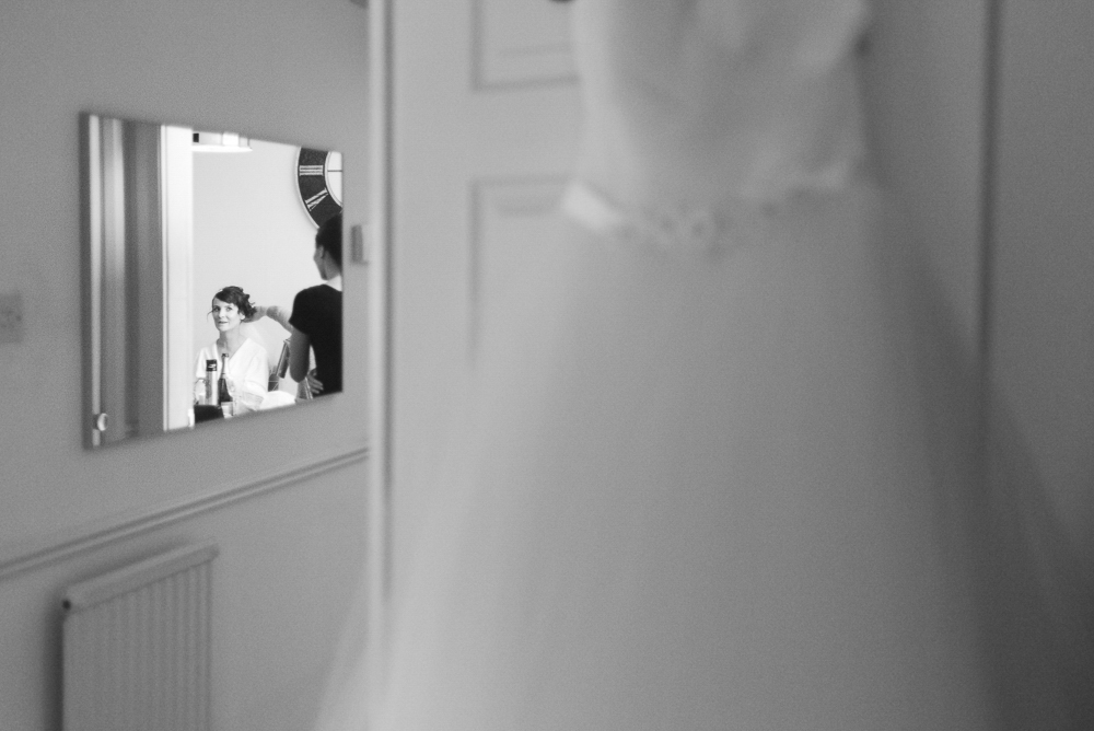 Bride getting ready reflected in mirror with wedding dress in foreground
