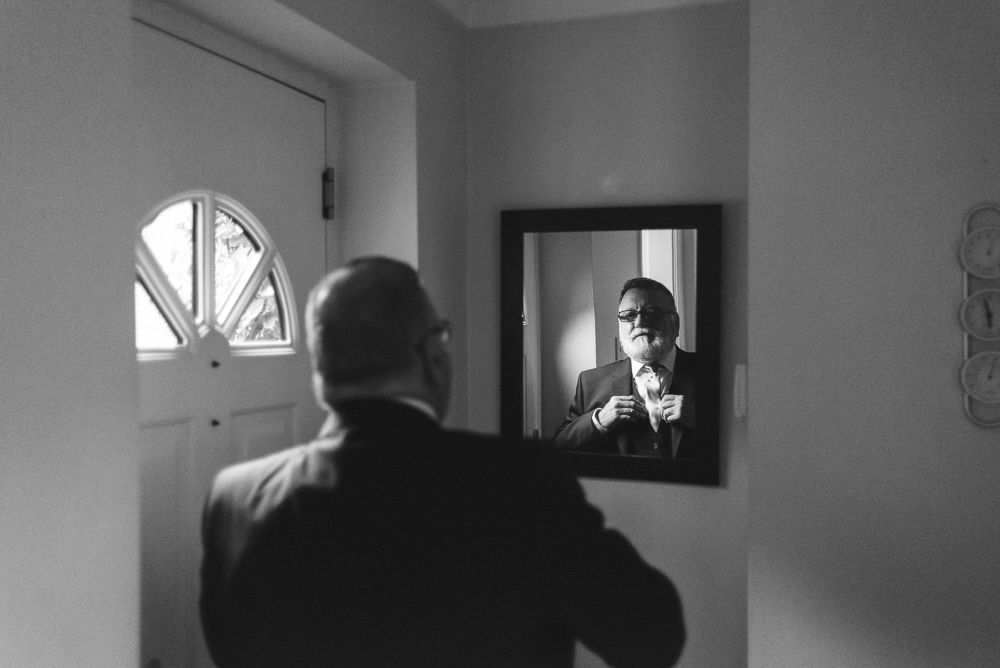 Father of the bride getting ready in the mirror