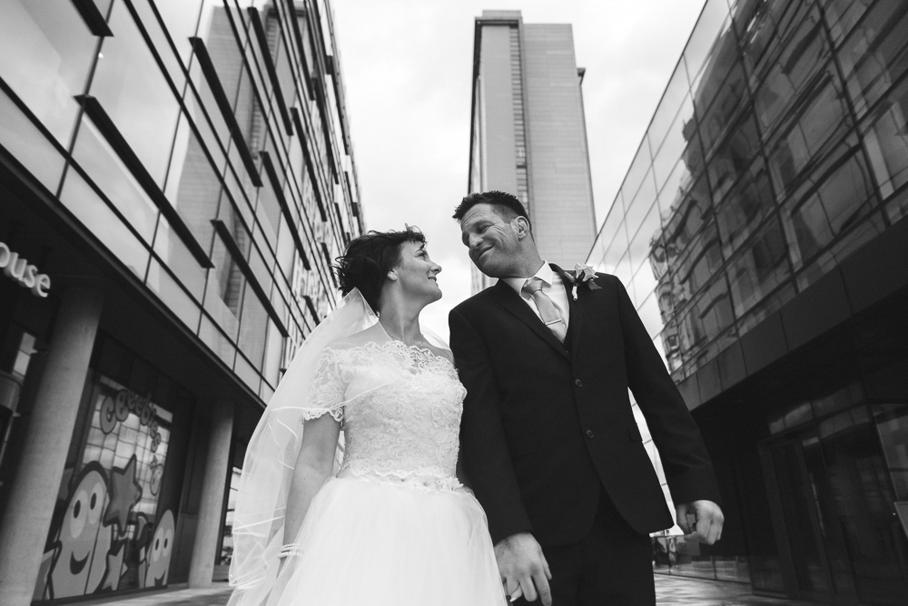 Bride and groom look at each other in Media City, Salford Wedding photographer