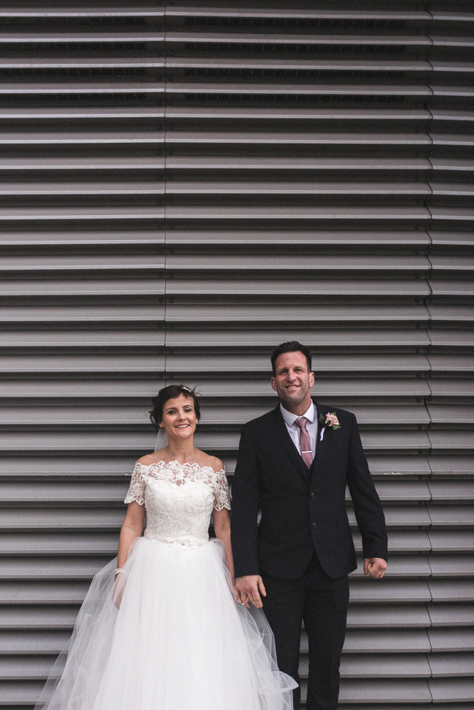Bride and groom look at the camera, Salford wedding photographer