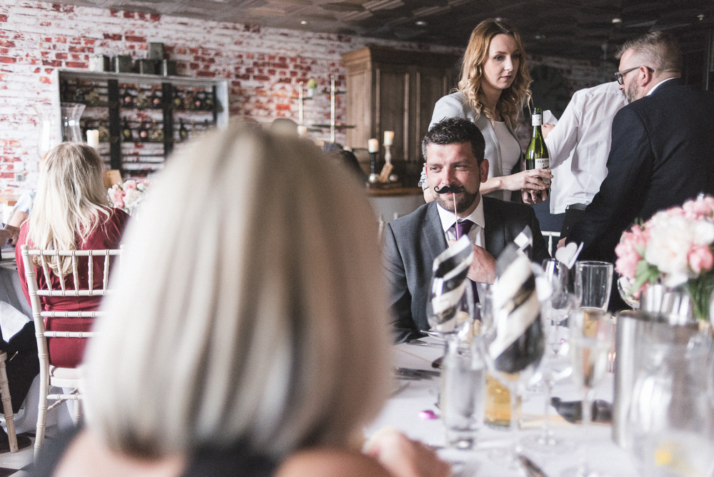 Guest holds a fake mustache in a Salford Wedding. Wedding Photography Salford