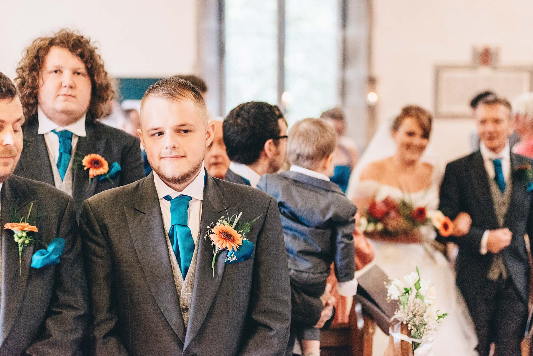 Groom waits nervously for bride walking up the aisle