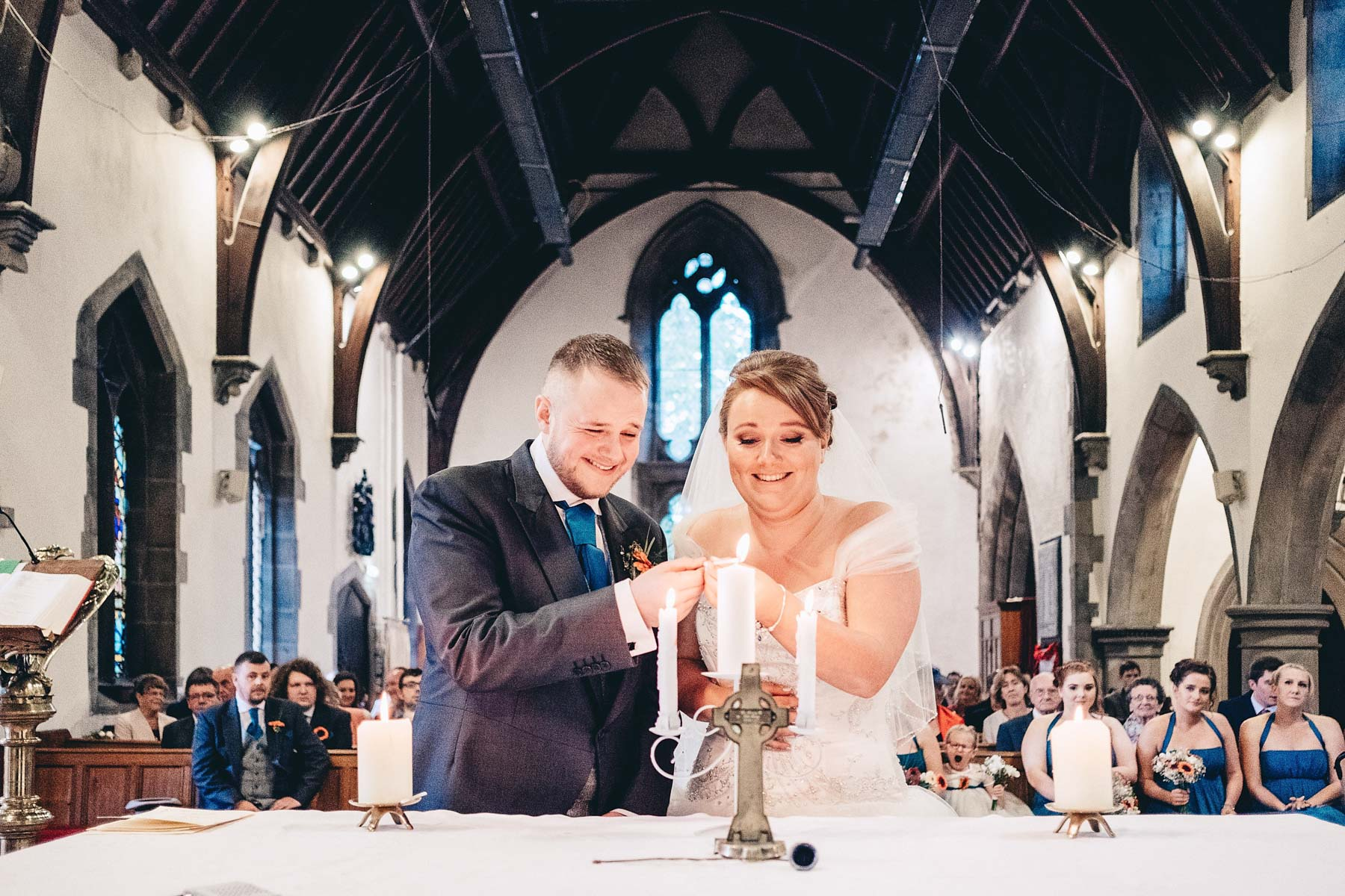 Bride and groom laugh as they light a candle in church