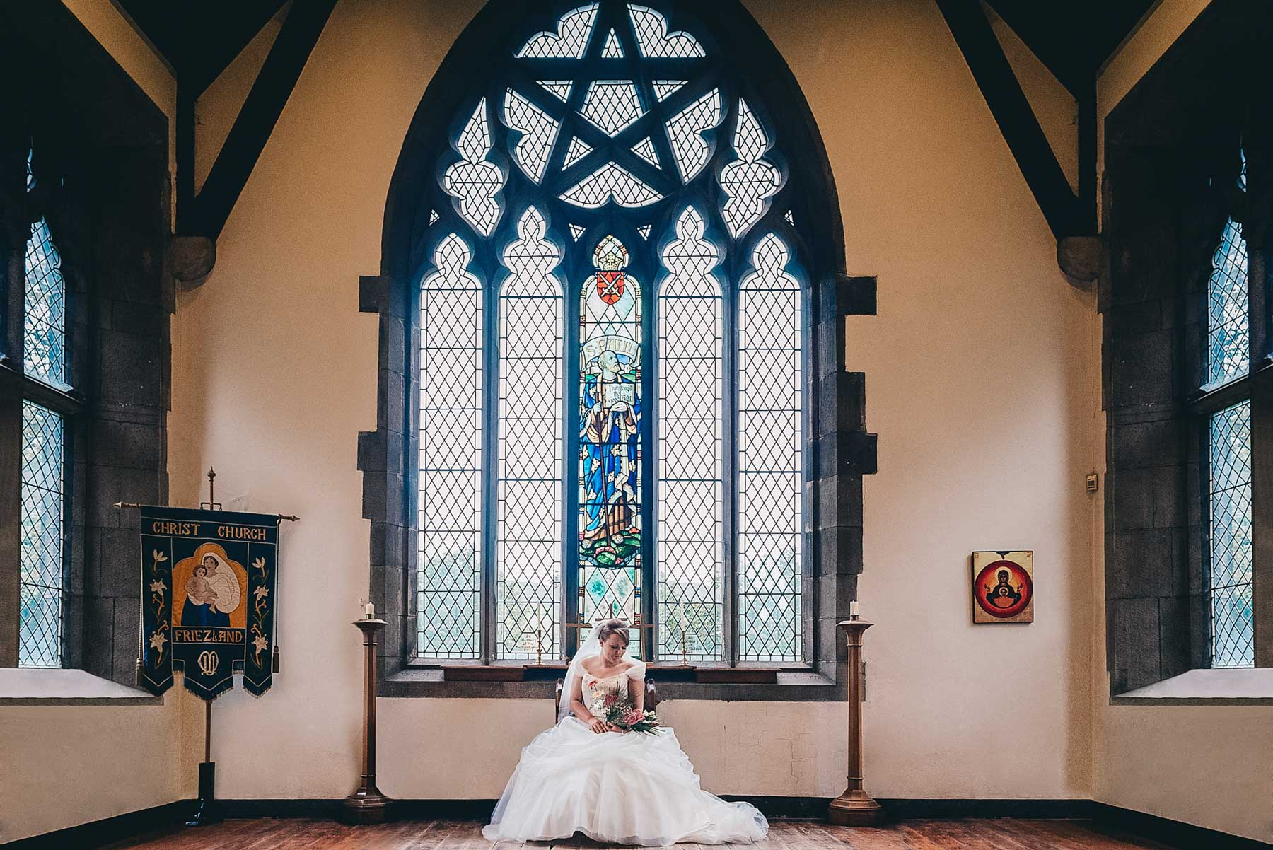 Bride looks down at flowers below grand church window