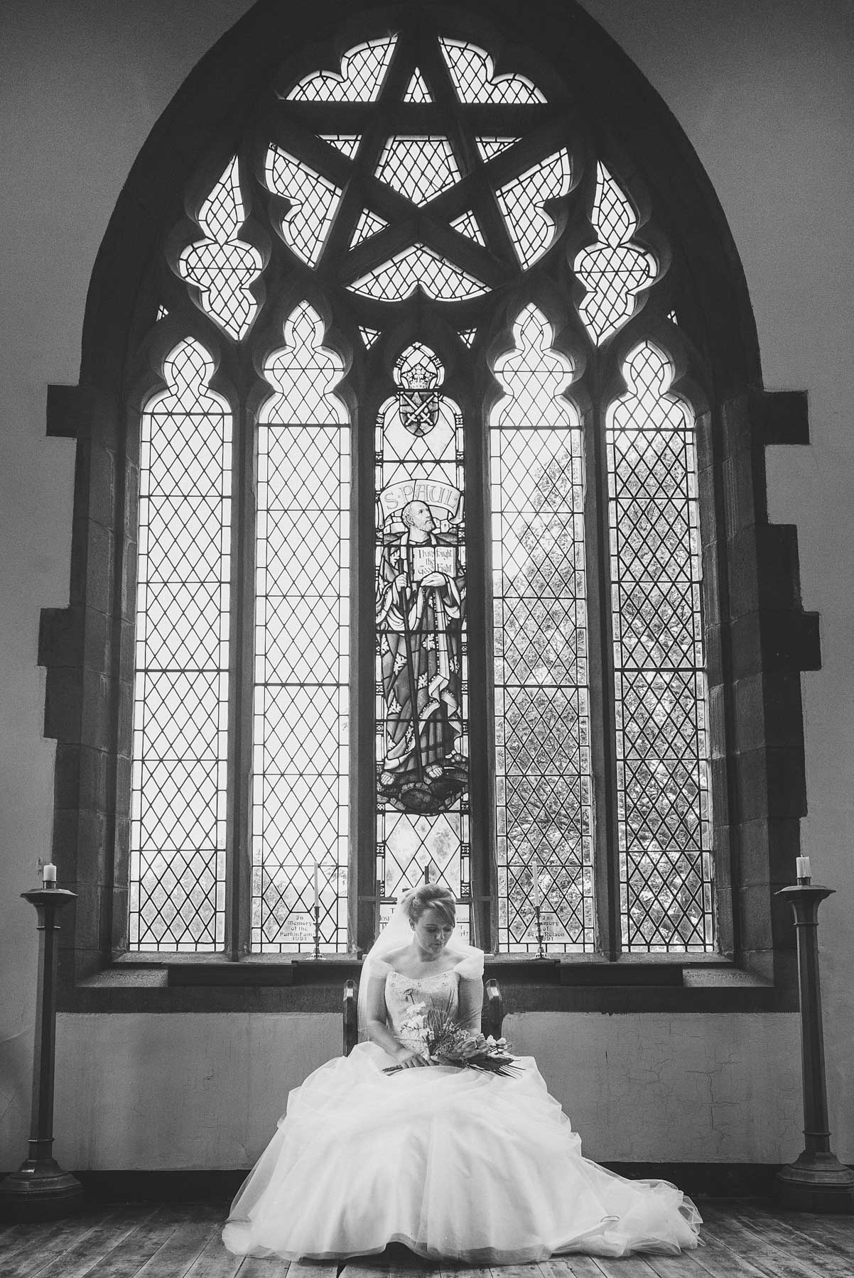 Bride looks at flowers underneath grand stain glass window
