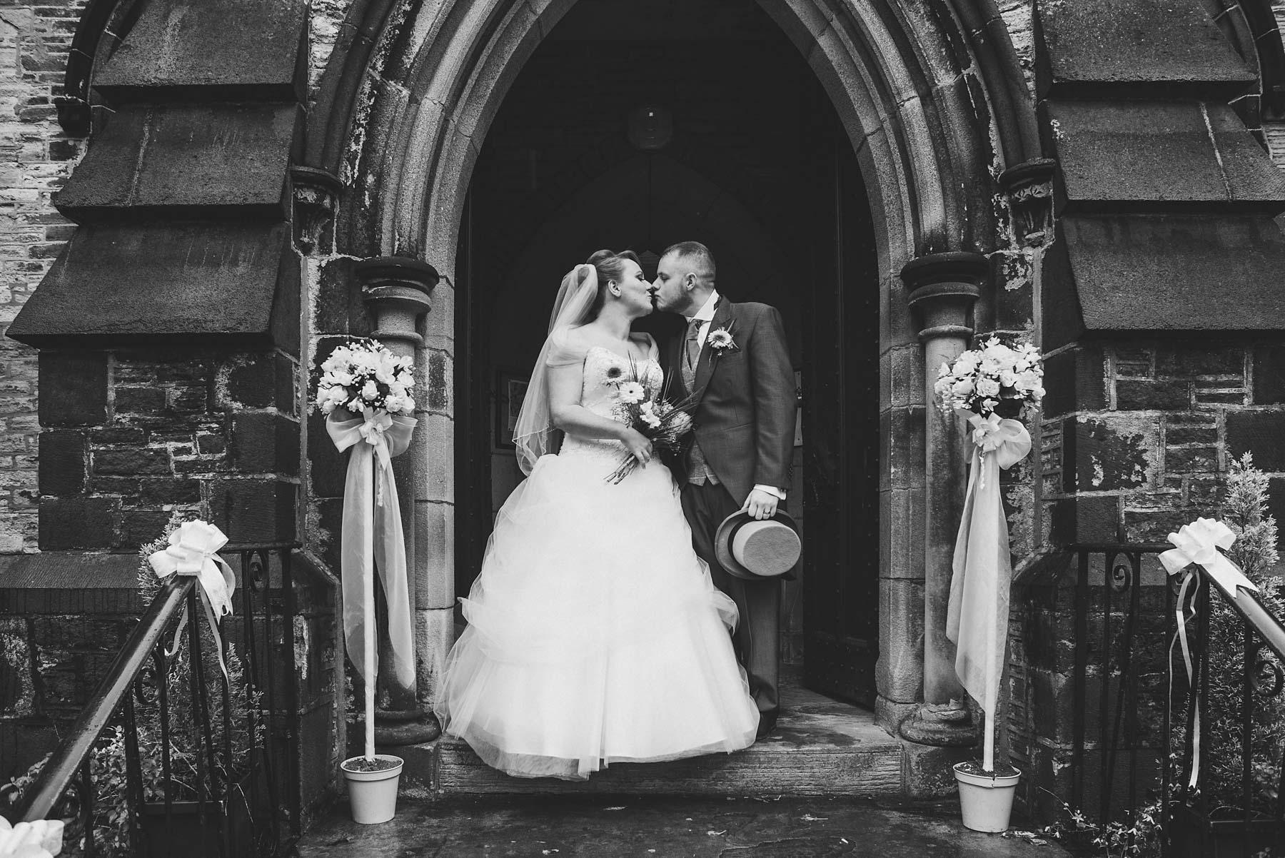Bride and groom kiss outside Friezland Church Saddleworth