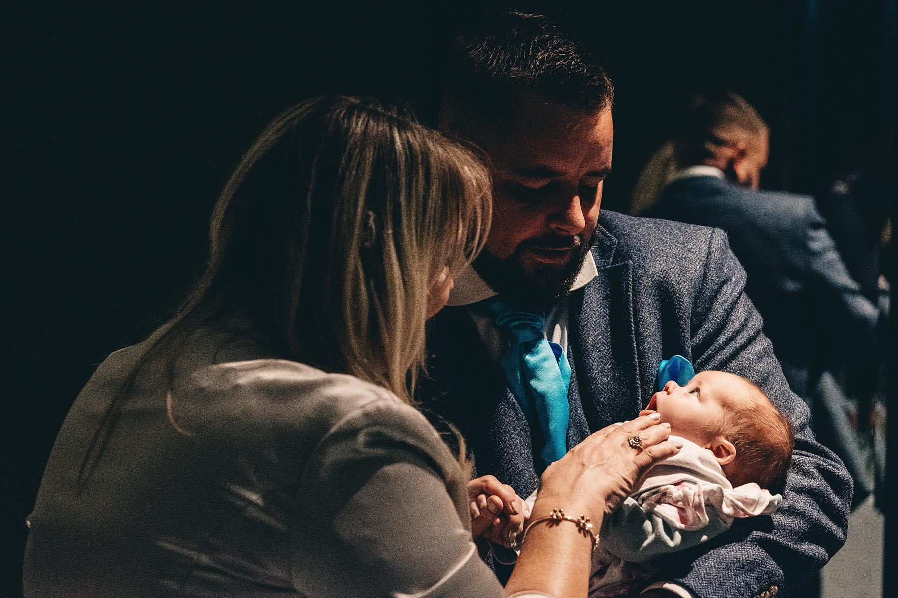 A couple play with a baby in a wedding reception