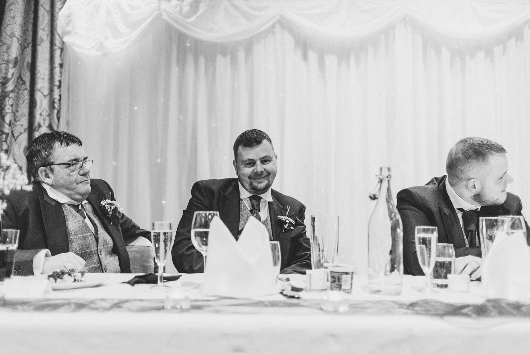 Groom and bestman look on during wedding speeches