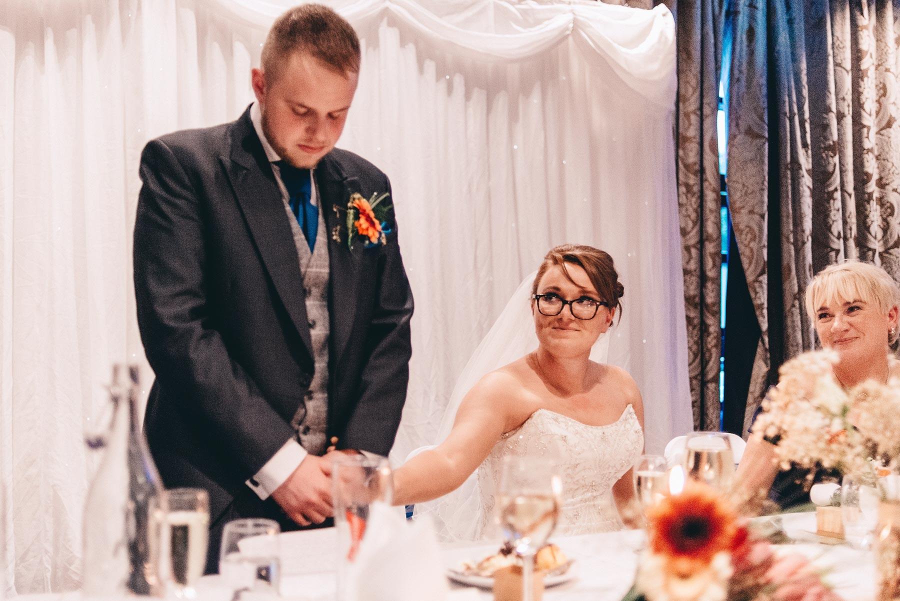 Bride looks at groom during emotional speech