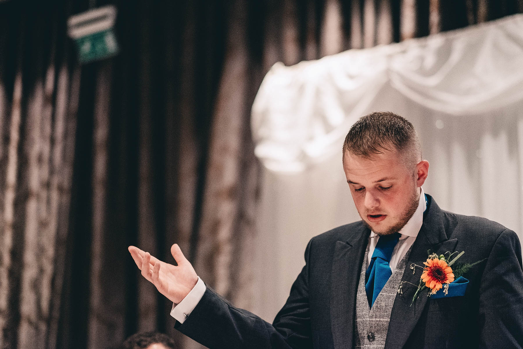 Groom holds his hand in the air during speech