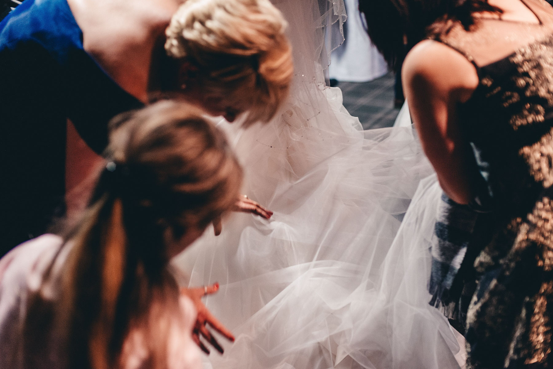 Guests help bride with her dress